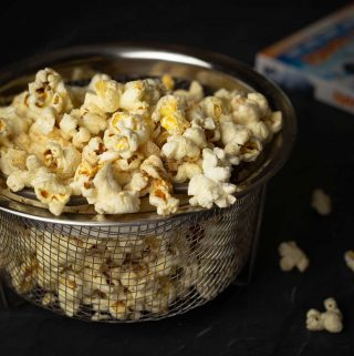 Ninja Foodi Popcorn in a mesh bowl with a DVD jacket behind it