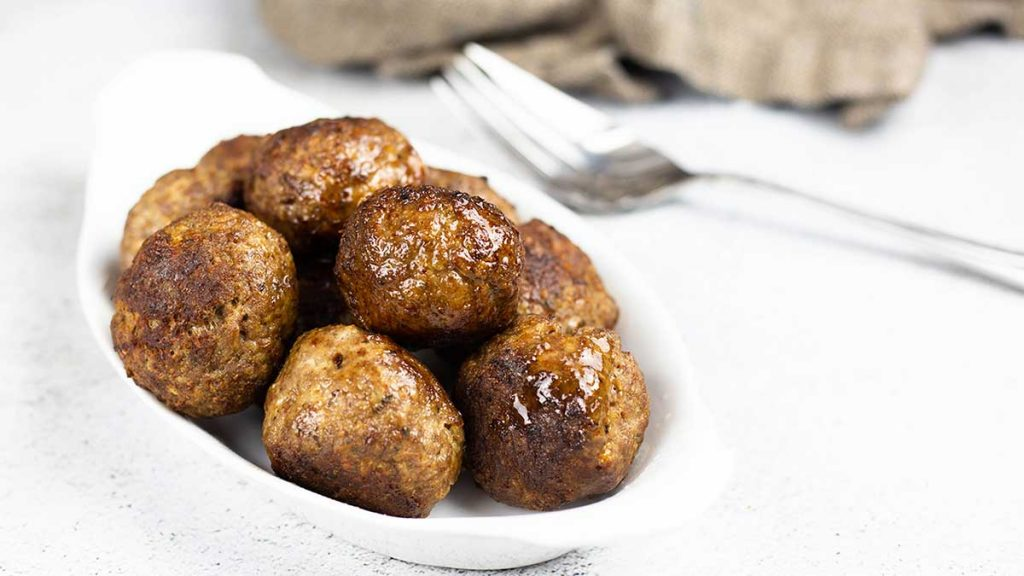 Meatballs in white bowl with a fork and napkin towards the back