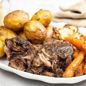 pot roast with potatoes and carrots on a white platter