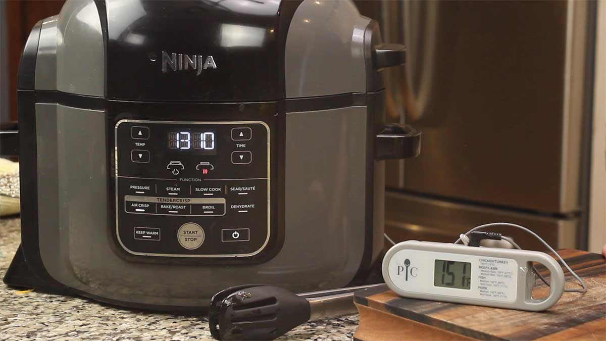 Pampered Chef Probe Thermometer sitting on cutting board with probe inside the Ninja Foodi