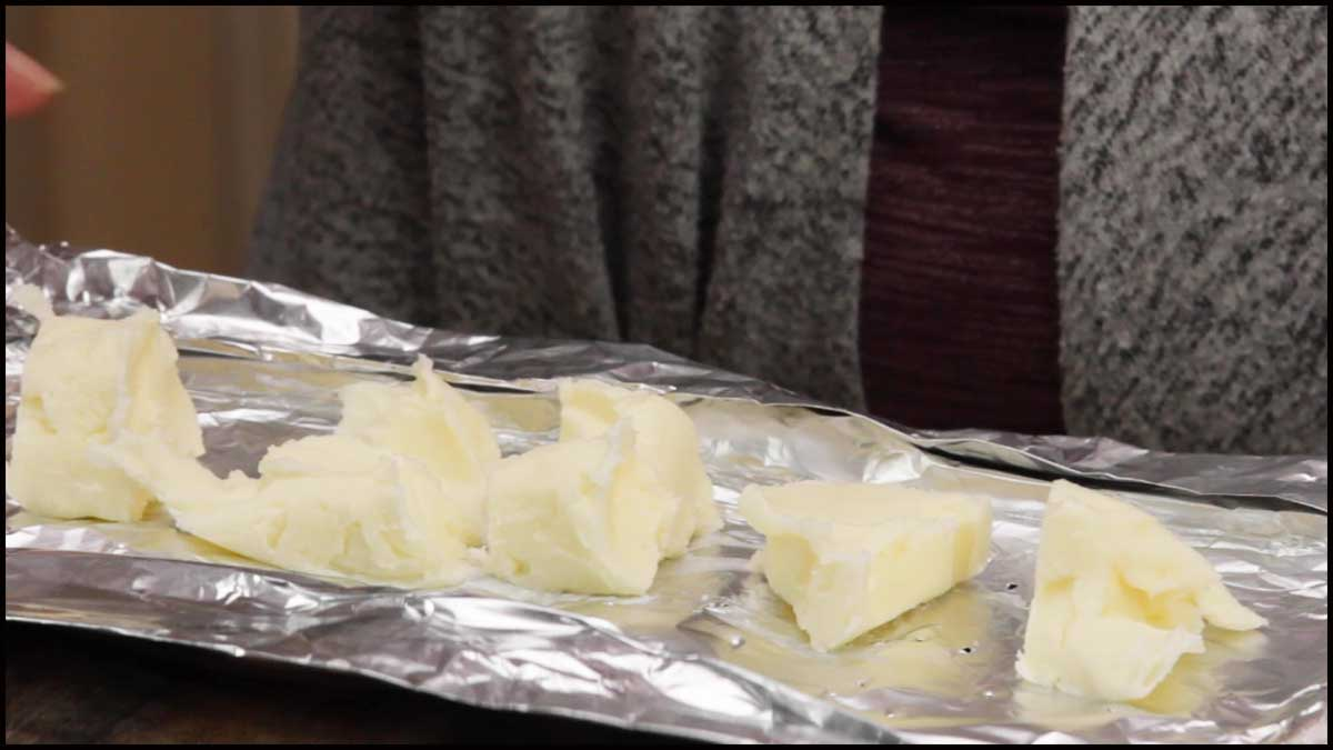 spreading butter over bottom of foil packet