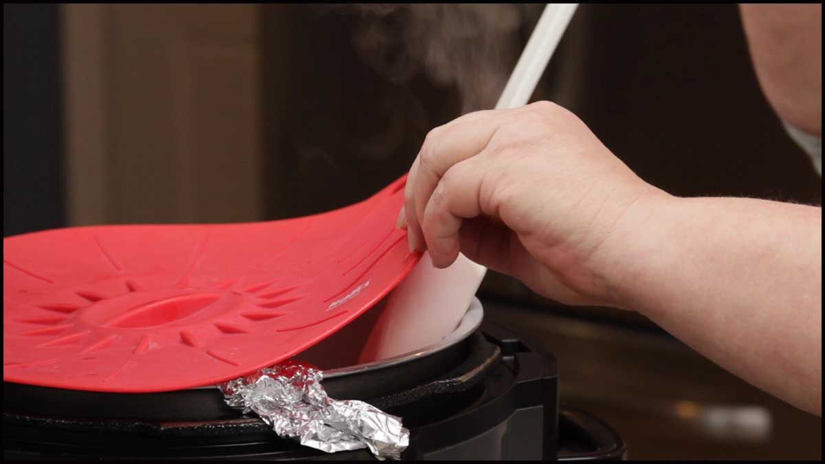 lifting the silicone lid to stir the popcorn as it starts to pop