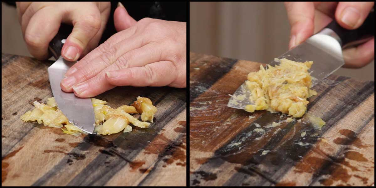 making garlic paste from roasted garlic on a cutting board with the back of a chefs knife