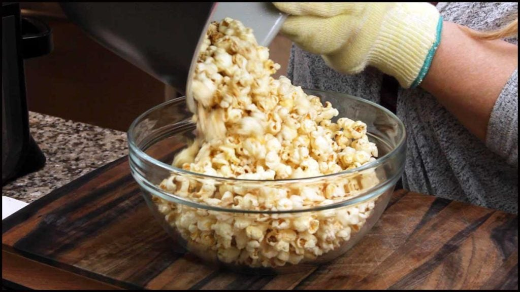 pouring Ninja Foodi Popcorn into a glass bowl for serving