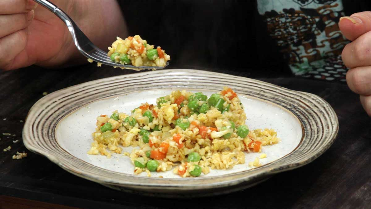 cauliflower fried rice on a plate and lifting a fork full of it