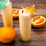Orange Milkshakes with sliced oranges next to them and a full orange