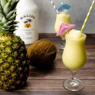 Pina Colada in a glass next to a pineapple and coconut