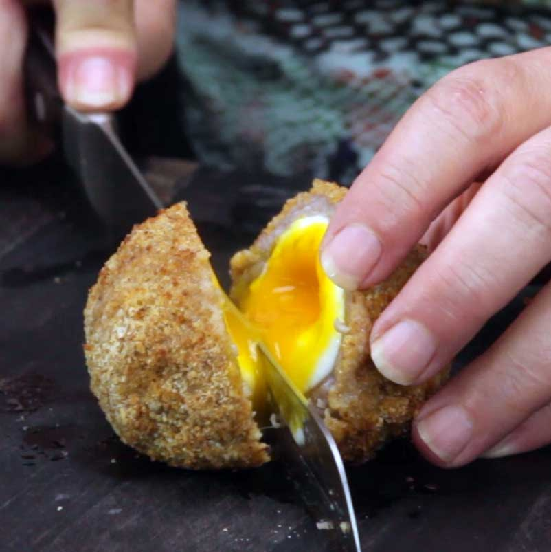 cutting open a scotch egg with a runny yolk