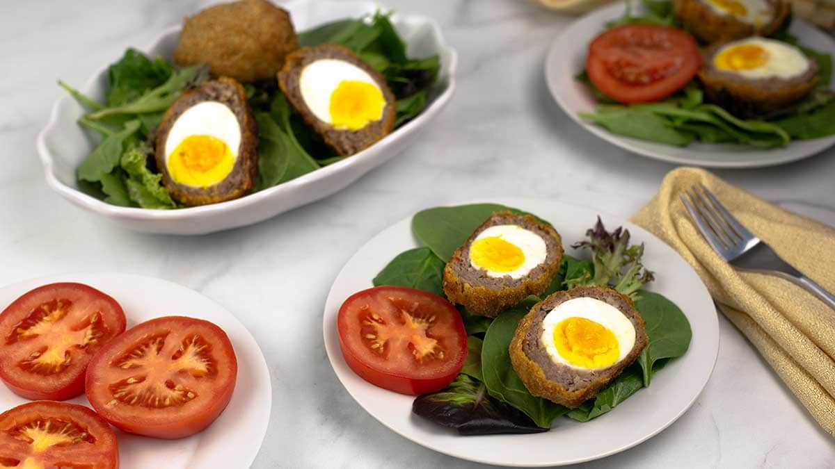 Scotch eggs cut in half sitting on a plate with spinach and tomatoes