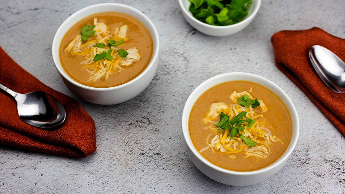 two bowls of creamy chicken enchilada soup with red napkins and spoons