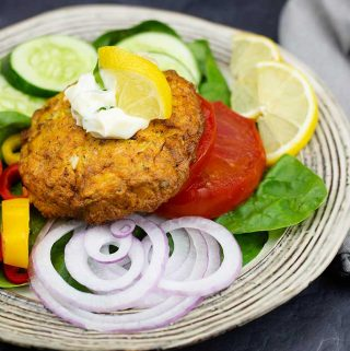 Salmon Patty on a salad with a bit of tarragon mayo and a lemon wedge