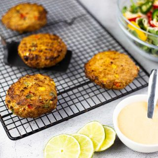 Southwest Turkey Burgers on a cooling rack next to a salad with a dressing and sliced lime