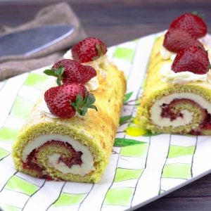 Strawberry roll cake cut in half on a platter