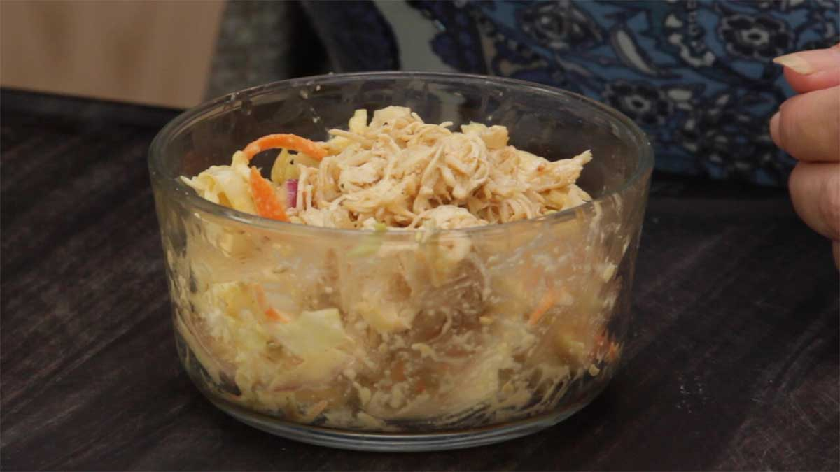 Asian Shredded Chicken in a bowl over Asian Slaw