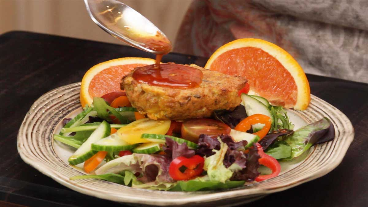 salmon patty on top of a salad with Asian dressing being spooned over it
