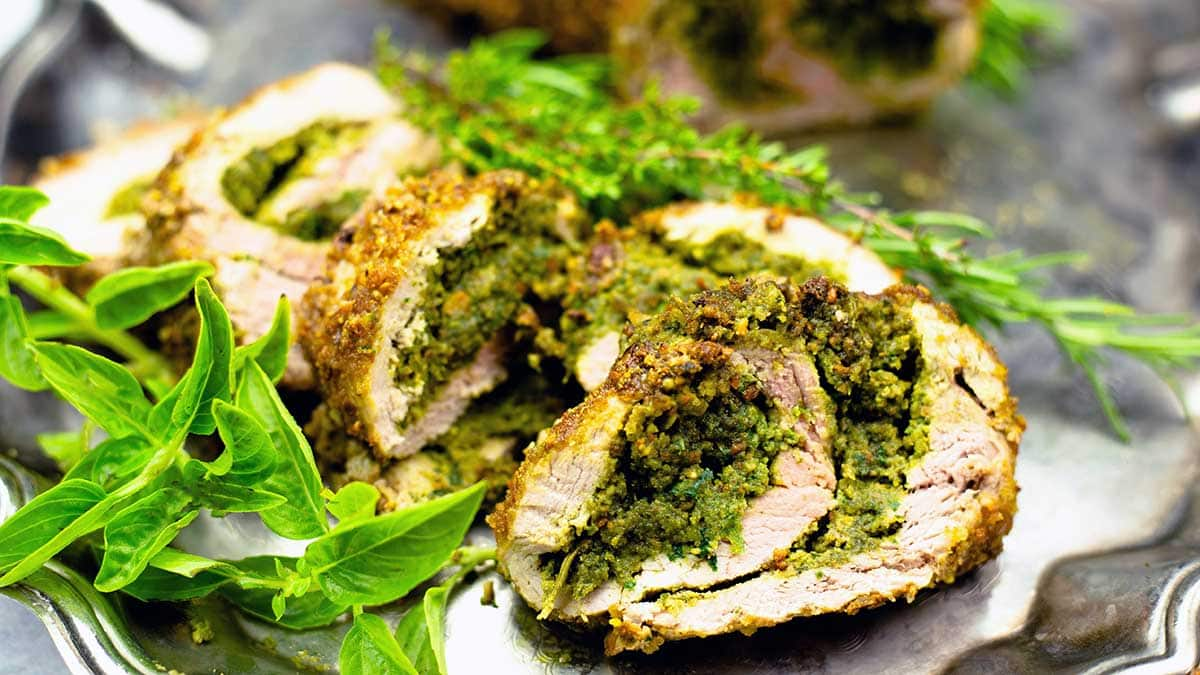 pesto stuffed pork tenderloin cut into slices on a platter