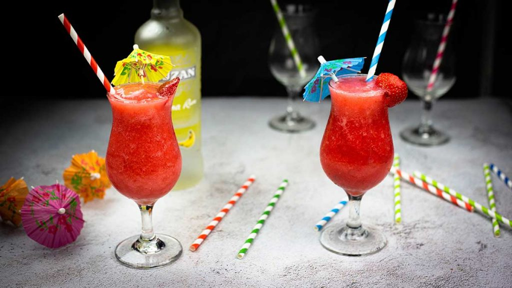 two strawberry daquiris in hurricane glasses with colored straws and drink umbrellas