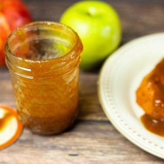 apple butter bourbon bbq sauce in a jar with a pork chop covered in bbq sauce