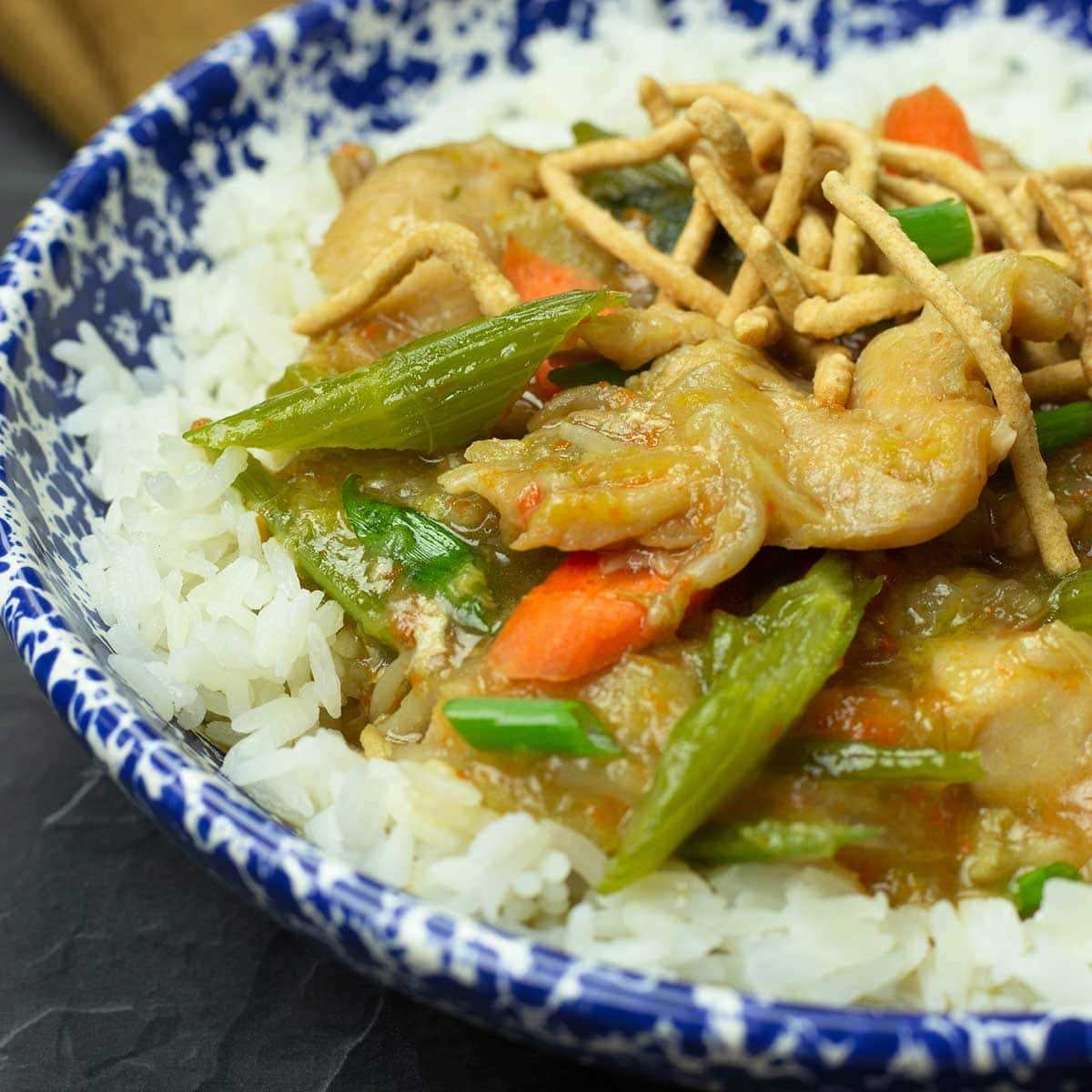Chicken Chop Suey over rice in a blue and white bowl