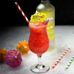 Frozen Strawberry Daiquiri in a hurricane glass with colored straws and drink umbrellas