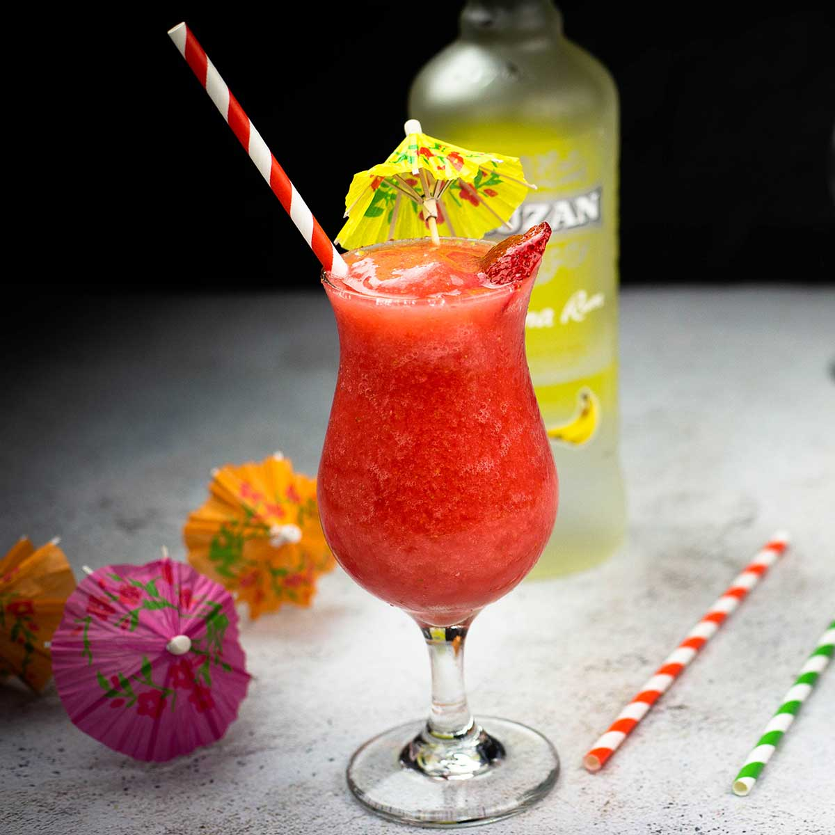 Frozen Strawberry Daiquiri in a hurricane glass with colored straws and drink umbrellas
