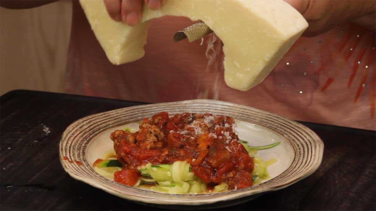 grating parmesan cheese over the top of zoodles and healthy spaghetti sauce