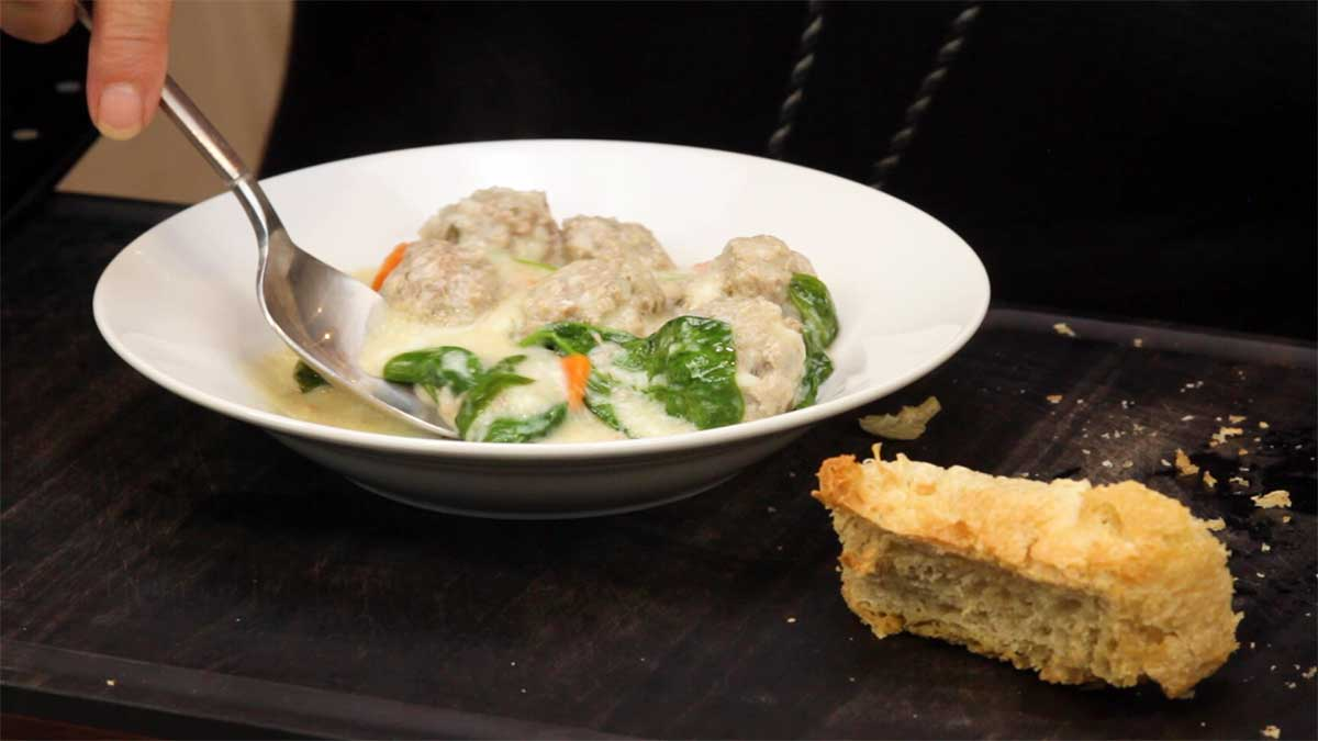 serving the greek meatball soup in a bowl with crusty bread