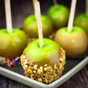 Homemade caramel apples on a tray, one is covered in nuts and one is covered in rainbow sprinkles