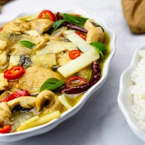 green curry chicken next to white rice in white bowls