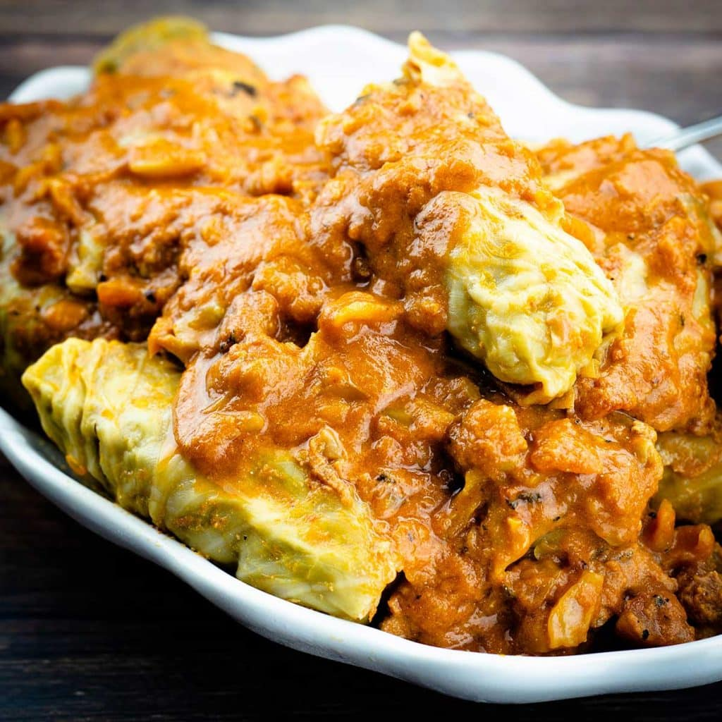 cabbage rolls with sauce over top in a white serving platter