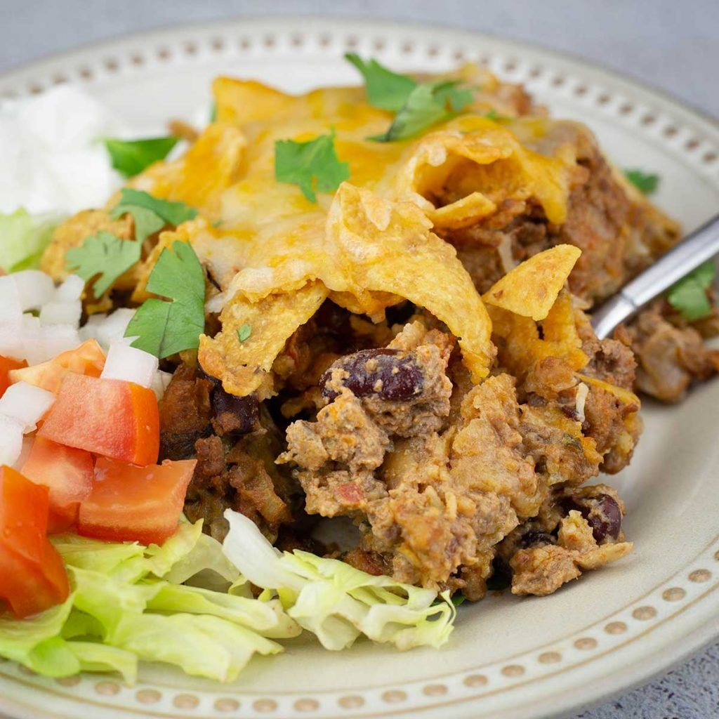 Walking taco casserole on a plate with lettuce, tomatoes, onions, and sour cream next to it