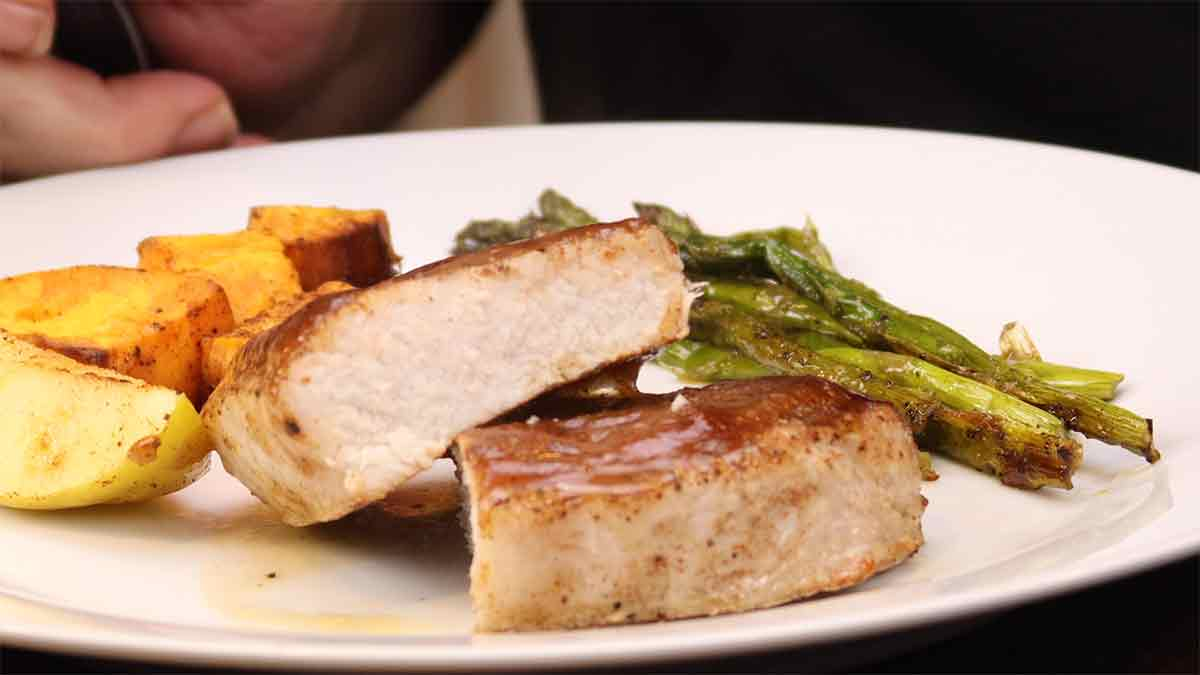 Pork chop cut in half on a plate with asparagus, apples, and sweet potatoes
