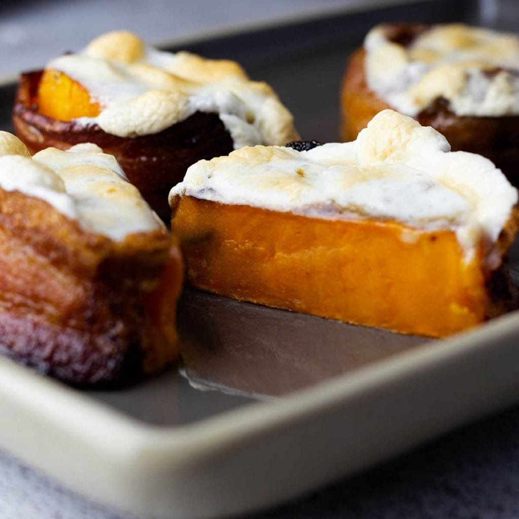 bacon wrapped sweet potatoes with melted marshmallows on top