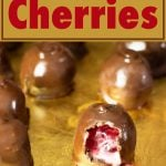 tray of chocolate covered cherries with one opened and the liquid center dripping out