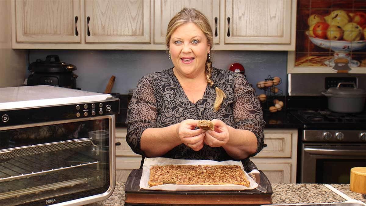 Louise holding a cut pecan pie bar