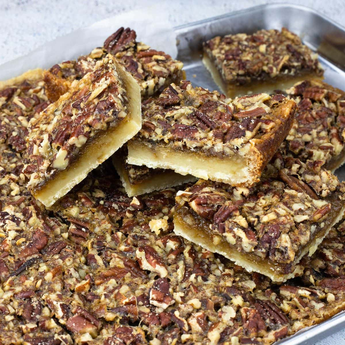 pecan bars cut and piled up on a sheet pan