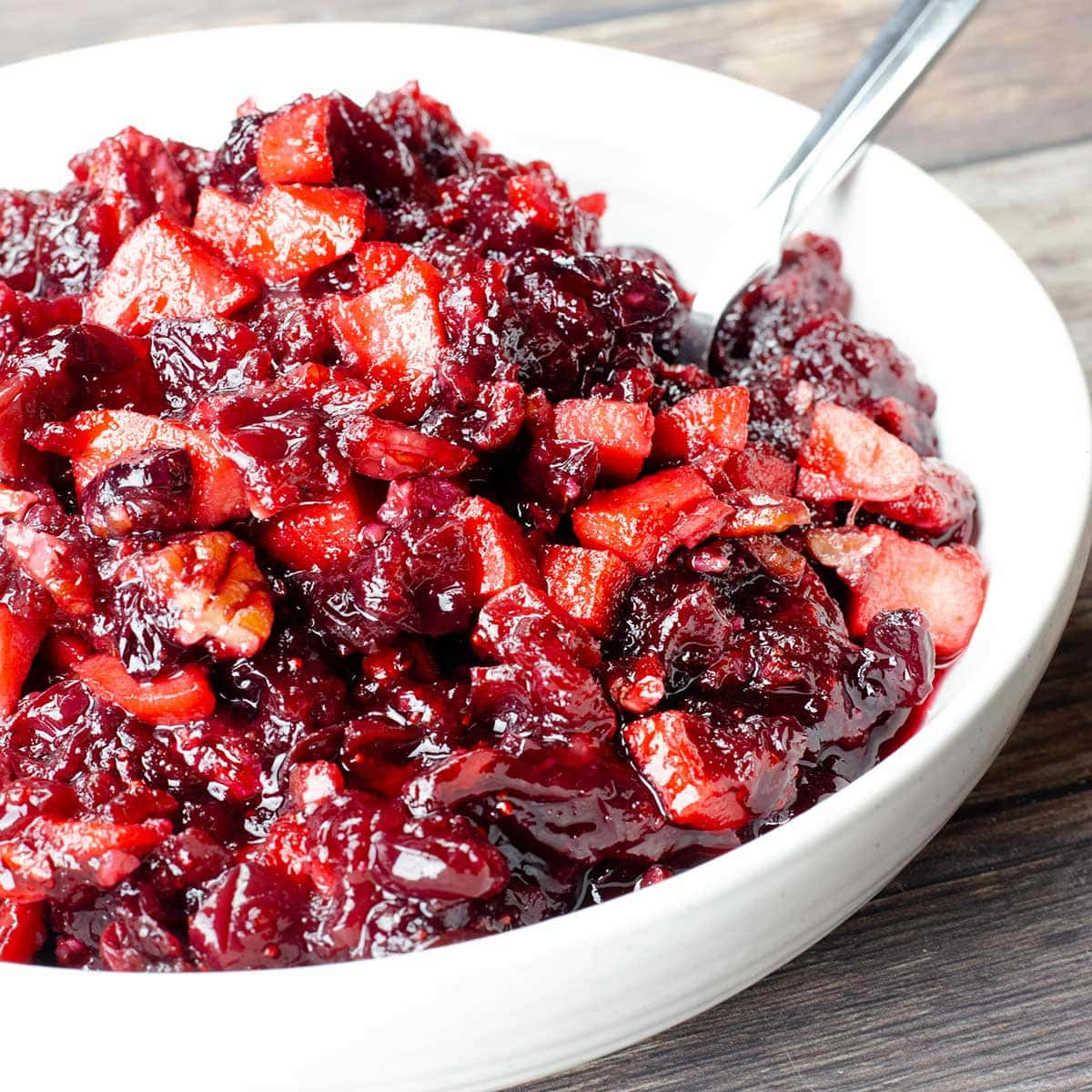 cranberry apple chutney in a white bowl with a spoon