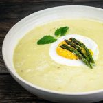 creamy asparagus soup in a bowl with an egg on top with basil and asparagus spears