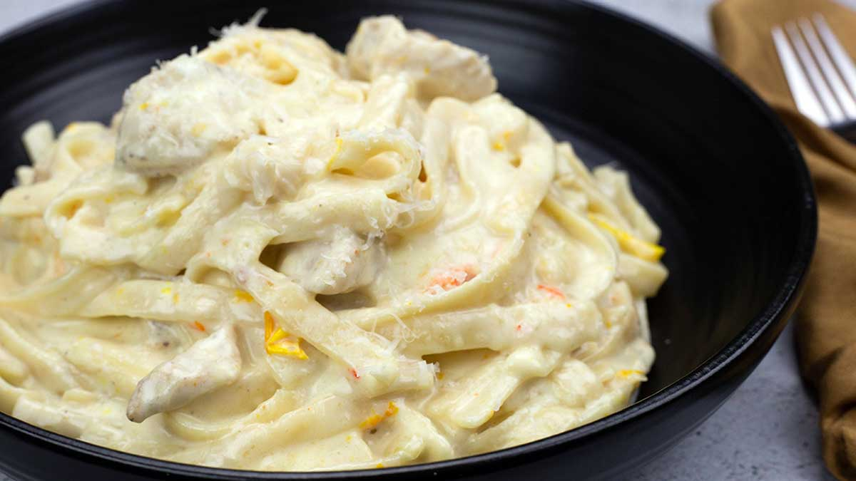 chicken alfredo in a black bowl