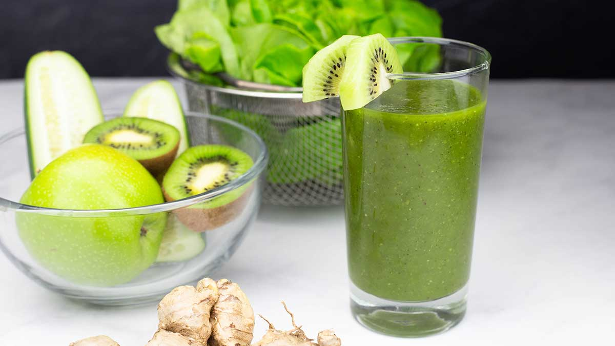 Green juice in a glass with fruit and vegetables behind it