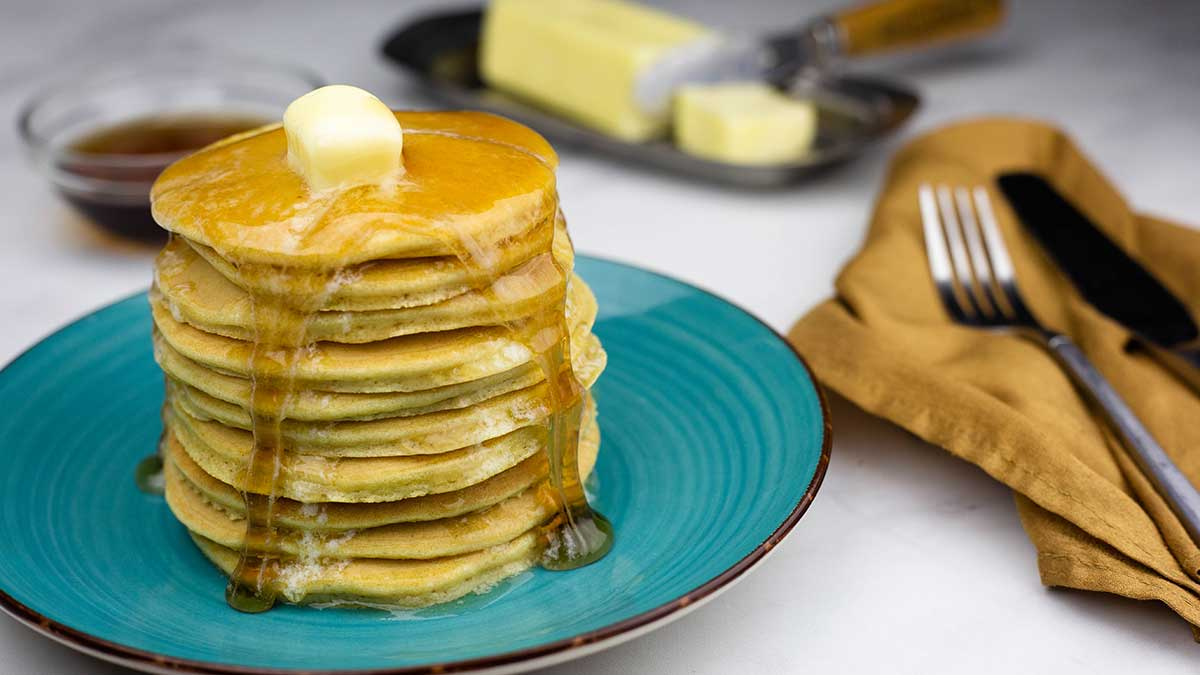 Keto pancakes stacked on a blue plate with butter and syrup dripping down the sides