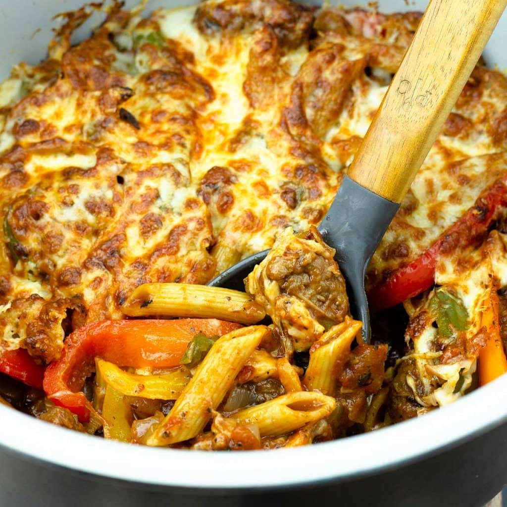 sausage peppers and pasta topped with cheese in the inner pot of the Ninja Foodi