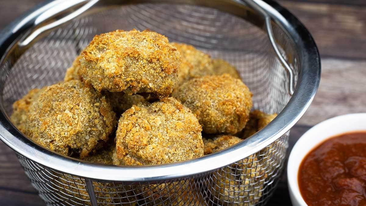 Air Fryer Fried Mushrooms in a basket next to marinara sauce