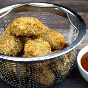 Air Fryer Fried Mushrooms in a basket next to marinara sauce