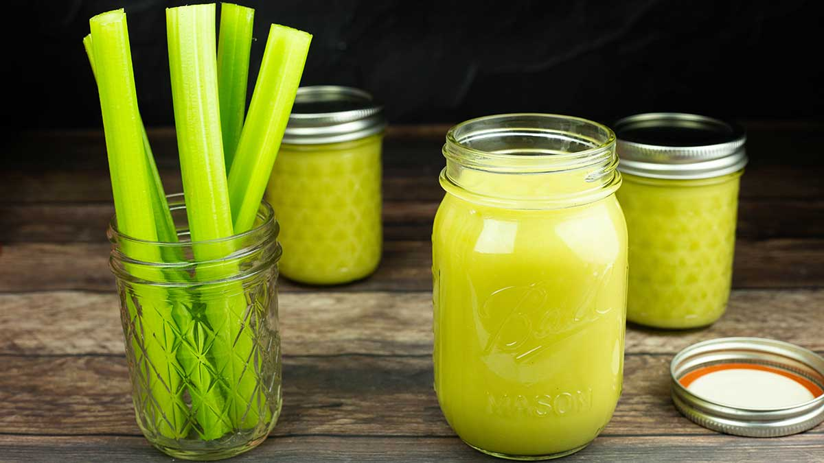 jars of condensed cream of celery soup next to a glass with celery stalks in it