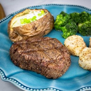 Filet, baked potato, scallops, and broccoli on a blue plate