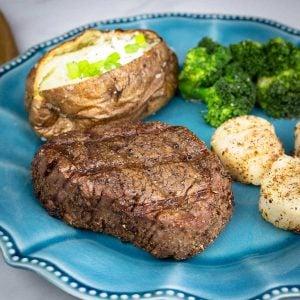 Filet, baked potato, scallops, and broccoli on a blue plate