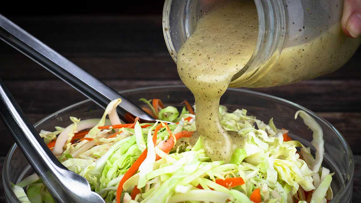 creamy coleslaw dressing being poured over shredded cabbage and carrots