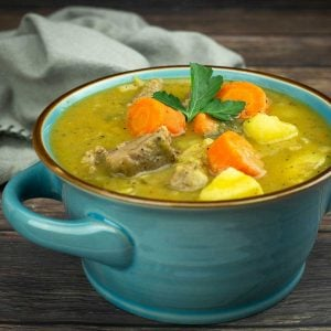 Irish stew in a blue bowl with parsley garnish