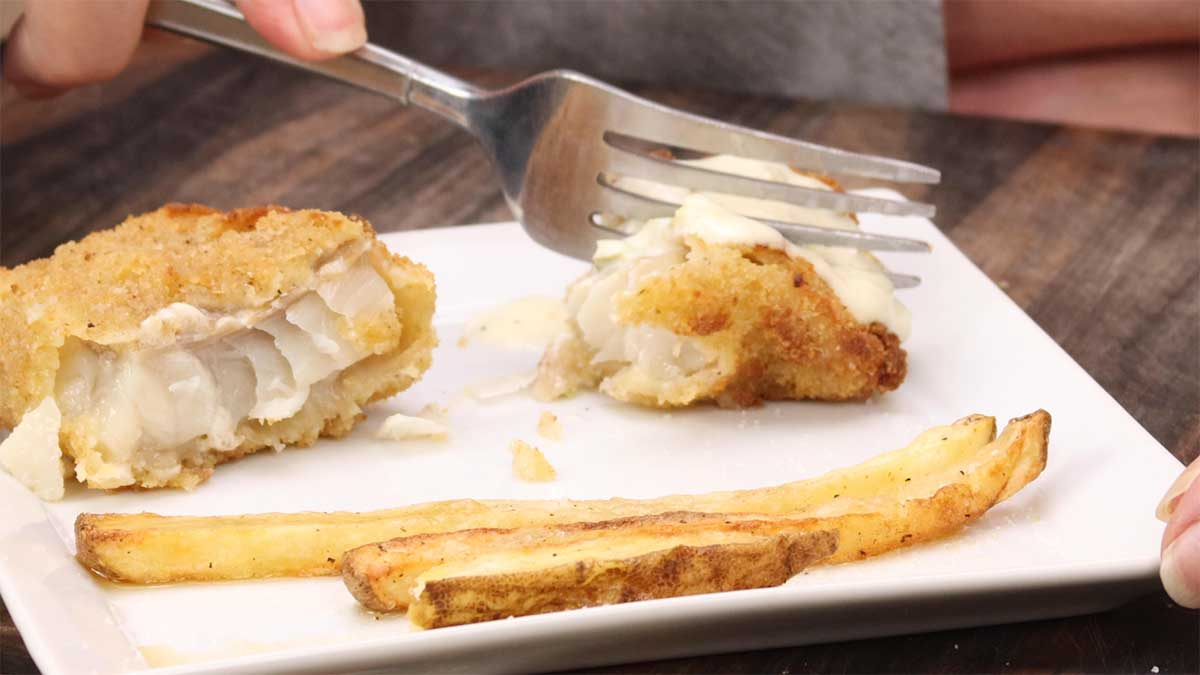 air fryer fish and chips on a plate with fish cut in half
